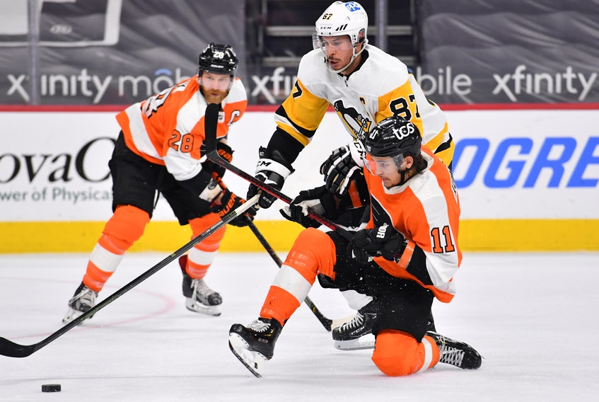 Pittsburgh Penguins centre Sidney Crosby and Philadelphia Flyers right-winger Travis Konecny battle for the puck during Tuesday's game at the Wells Fargo Center in Philadelphia. - Eric Hartline-USA TODAY Sports