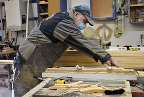 Robbie Lynds cutting wood at his tool- and material-filled workshop in Valley, Colchester County.