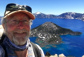 William Monk poses by Crater Lake in Oregon, which is the deepest lake in the United States. - Contributed