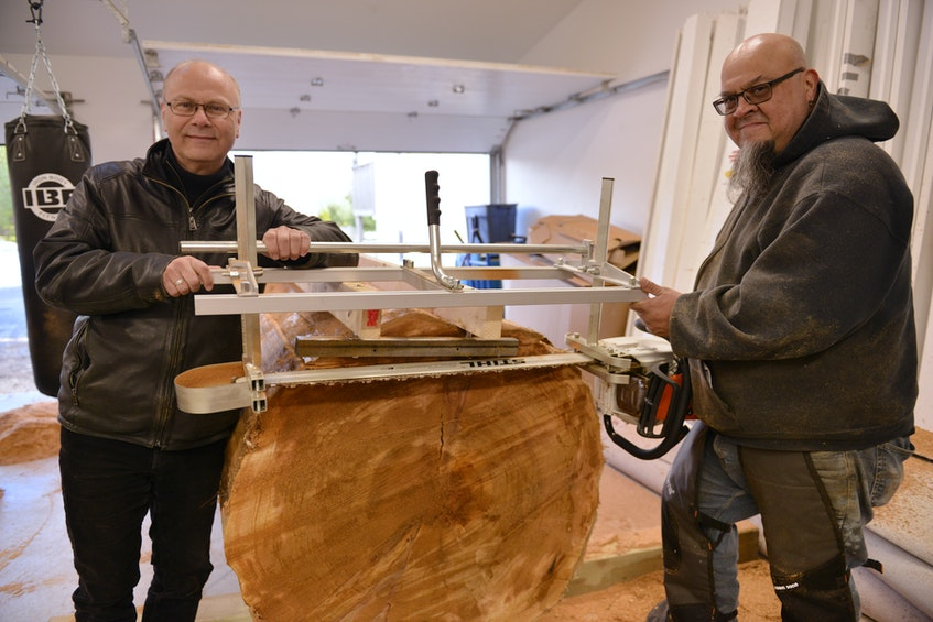 Friends United founder Rolf Bouman and West Coast woodcarver Gerry Sheena in Sheena's workshop in 2020. Sheena is working on a larger piece of red cedar for his next totem pole that will be displayed at the Friends United gallery in Richmond County. CONTRIBUTED - Ardelle Reynolds