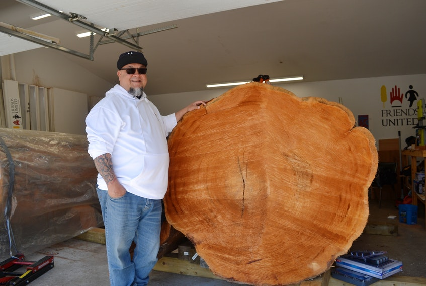 This almost 500-year-old red cedar was shipped to Cape Breton from British Columbia and will soon be carved into a totem pole and be displayed at the Friends United gallery in Cleveland, Richmond County. West Coast carver, Gerry Sheena, poses beside it for scale. ARDELLE REYNOLDS • CAPE BRETON POST