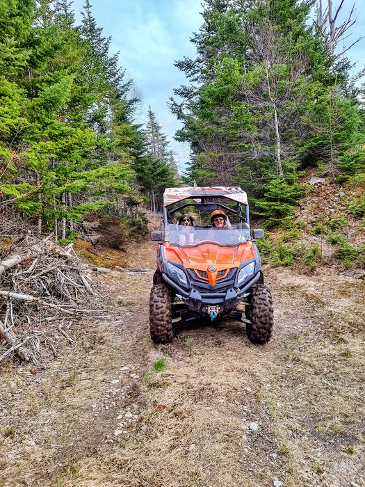 Isle Royale ATV Club president Judy Giovannetti enjoys a trail ride on her ATV with her dog Meca. CONTRIBUTED