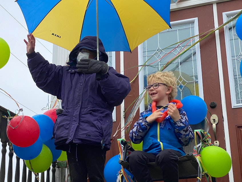 Joshua Petrone and his grandmother, Mette, wave to people who drove by beeping their horns and shouting birthday greetings to the 7-year-old on May 4. CARLA ALLEN • TRICOUNTY VANGUARD