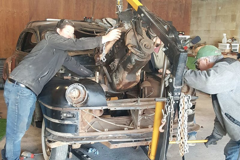 Members of the Torque Masters Car Club separate the engine from the 1947 Chrysler coupe as restoration work began. Ken Coward photo - POSTMEDIA