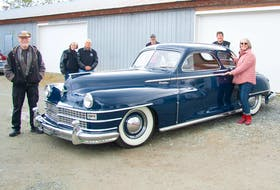 Saanich Peninsula Hospital Foundation executive director Karen Morgan with members of the Torque Masters Car Club that restored the 1947 Chrysler coupe to enhance the lives of dementia patients. Ken Coward photo