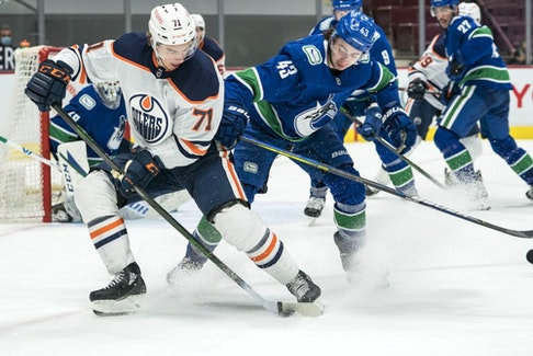 Vancouver Canucks defenseman Quinn Hughes (43) checks Edmonton Oilers forward Ryan McLeod (71) in the third period at Rogers Arena. Oilers won 5-3 on May 4, 2021.