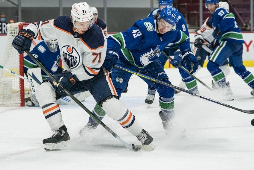 Vancouver Canucks defenseman Quinn Hughes (43) checks Edmonton Oilers forward Ryan McLeod (71) in the third period at Rogers Arena. Oilers won 5-3 on May 4, 2021.