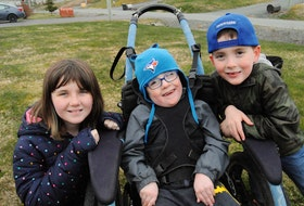 Lyndon Andersen, 5, (centre) with his sister Kaylee, 11, and twin brother, Zander, outside their Bay Bulls home on Friday afternoon. Joe Gibbons • The Telegram