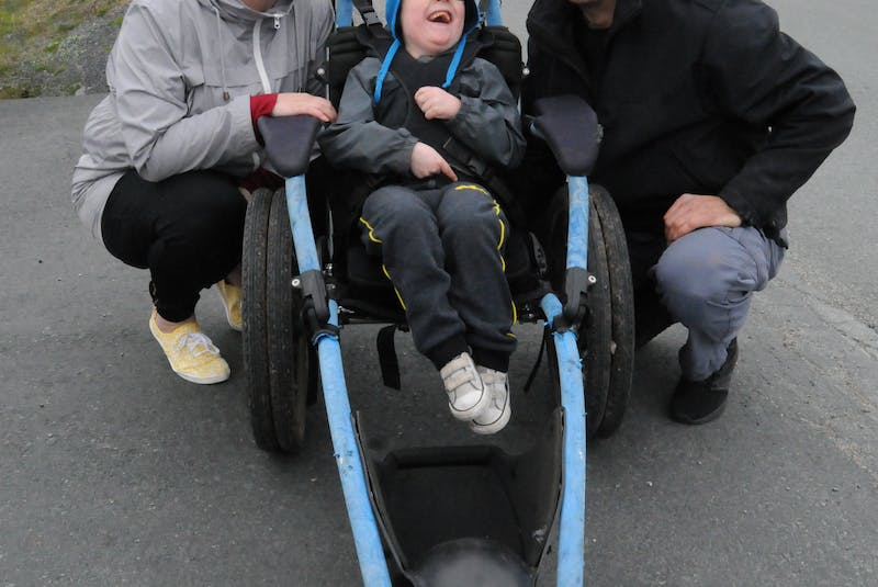 Lyndon Andersen, 5, with his parents, Adina Stamp and William Andersen, outside their Bay Bulls home on Friday afternoon, as he sits in a Hippocampe wheelchair borrowed from the Janeway children's hospital. Joe Gibbons • The Telegram - Joseph Gibbons