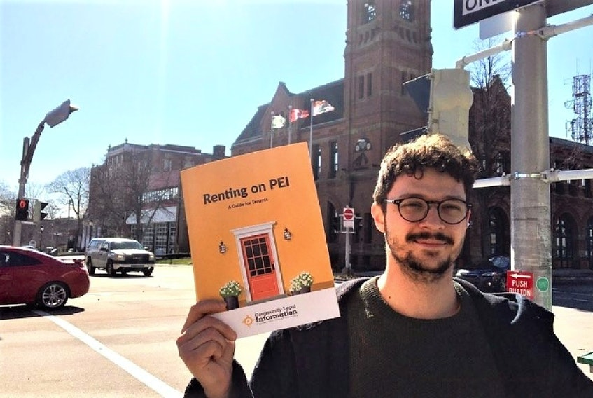 David McQuillan, 27, holds up a copy of the free handbook on tenants' rights. Copies are available at the public library.