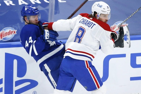 Canadiens' Ben Chiarot hits Maple Leafs defenceman Morgan Rielly during Thursday's game in Toronto.