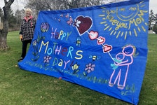 "Barb Chiasson stands next to the Mother's Day banner she painted and hung outside her Coxheath home. While the tattoo artist has the sign on display for all mothers, she made it for her mother who lives in Ontario. Chiasson stood with her head peeking over the sun in the photo for her mom. ""Oh, she cried,"" she said with a smile on Friday when asked if she'd pose for a picture with her latest artwork. Along with the Mother's Day sign, Chiasson puts up decorations for all holidays including Easter, Halloween and Christmas. For the anniversary of the mass shooting in Portapique, N.S., Chiasson put signs on the telephone poles near her home which read, ""All you need is love"" — the popular song by The Beatles. NICOLE SULLIVAN/CAPE BRETON POST"