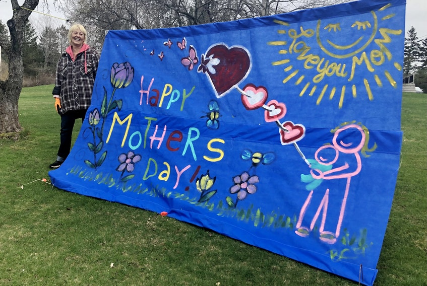 """Barb Chiasson stands next to the Mother's Day banner she painted and hung outside her Coxheath home. While the tattoo artist has the sign on display for all mothers, she made it for her mother who lives in Ontario. Chiasson stood with her head peeking over the sun in the photo for her mom. """"Oh, she cried,"""" she said with a smile on Friday when asked if she'd pose for a picture with her latest artwork. Along with the Mother's Day sign, Chiasson puts up decorations for all holidays including Easter, Halloween and Christmas. For the anniversary of the mass shooting in Portapique, N.S., Chiasson put signs on the telephone poles near her home which read, """"All you need is love"""" — the popular song by The Beatles. NICOLE SULLIVAN/CAPE BRETON POST"""