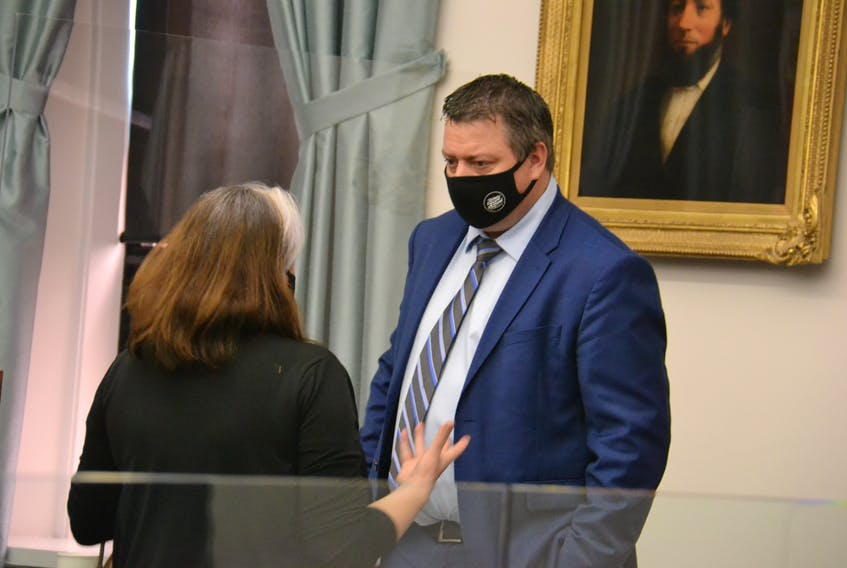 """Economic Growth Minister Matthew MacKay speaks to Green MLA Hannah Bell in the legislature. MacKay said the province will eventually implement more mandated paid sick days, but said P.E.I. businesses are now """"hanging on by a thread""""."""