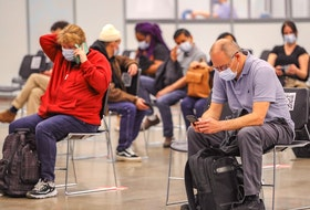 People sit in the post-vaccination waiting area at the COVID-19 vaccination clinic at the Palais des congrés in Montreal Tuesday May 4, 2021.