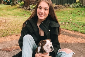 """Abby Falkenham relaxes in Upper Stewiacke with her dog """"Gus."""""""