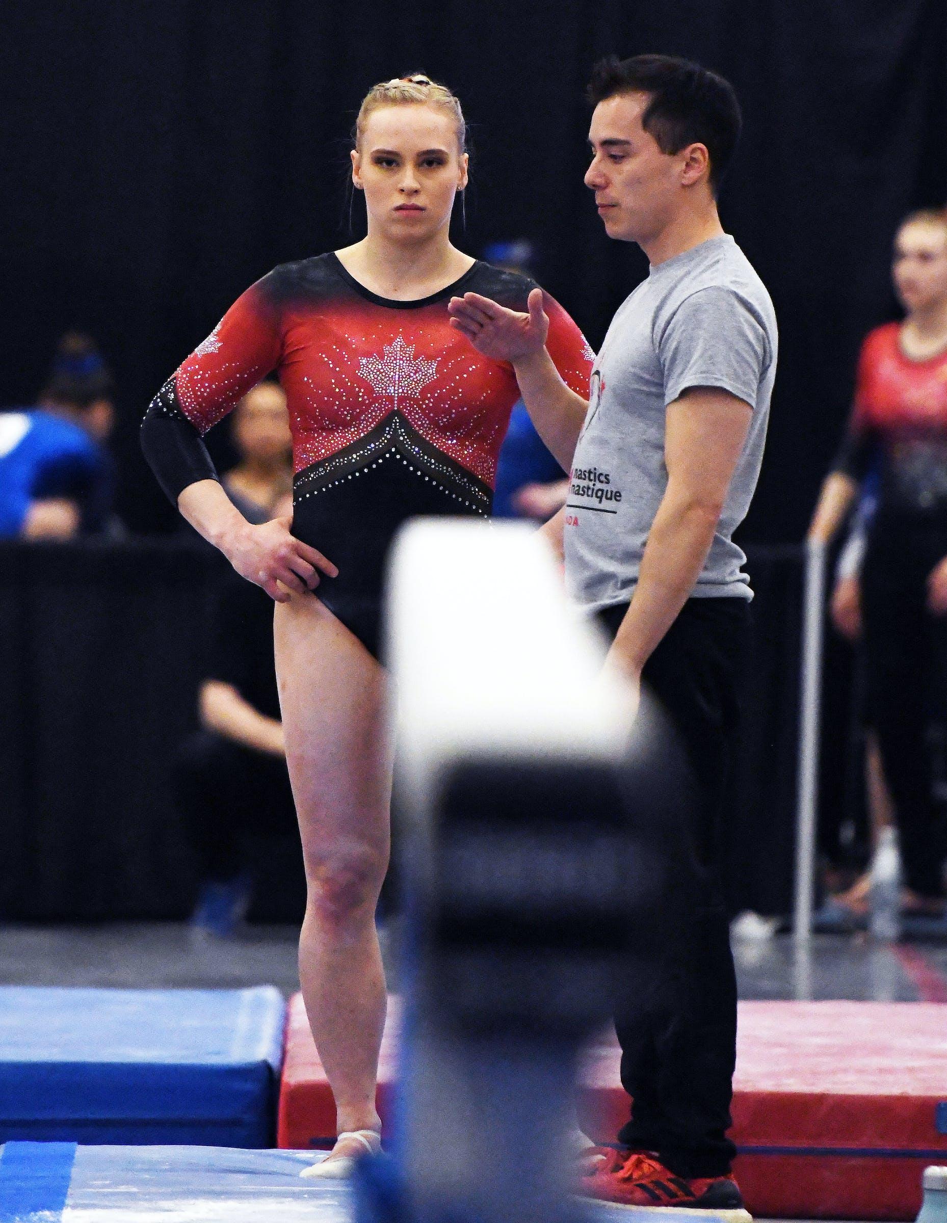 Ellie Black focuses as coach David Kikuchi gives instruction at the 2019 Artistic Gymnastics Canadian Championships in Ottawa. - Gymnastics Canada