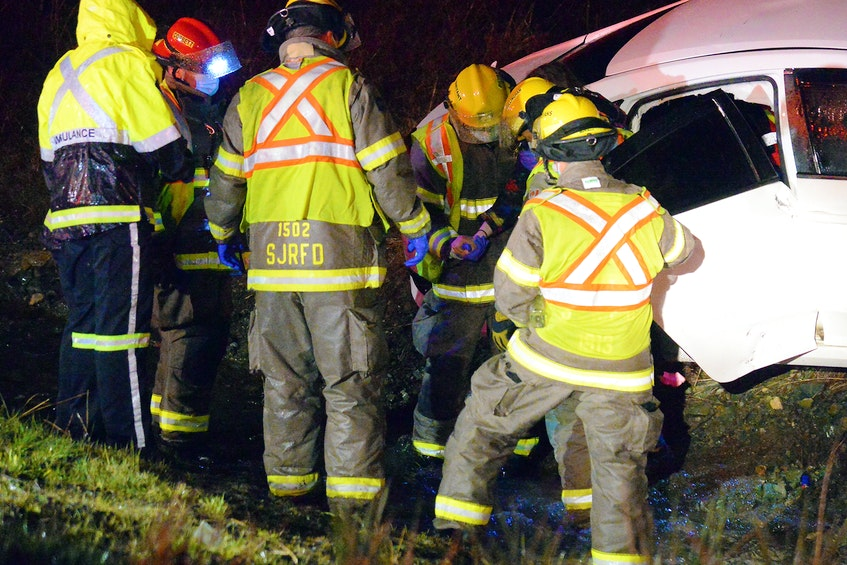 First responders walk a woman to a waiting ambulance after her car crashed over an embankment at the Peacekeepers Way/Pitts Memorial cloverleaf Saturday night. Keith Gosse/The Telegram
