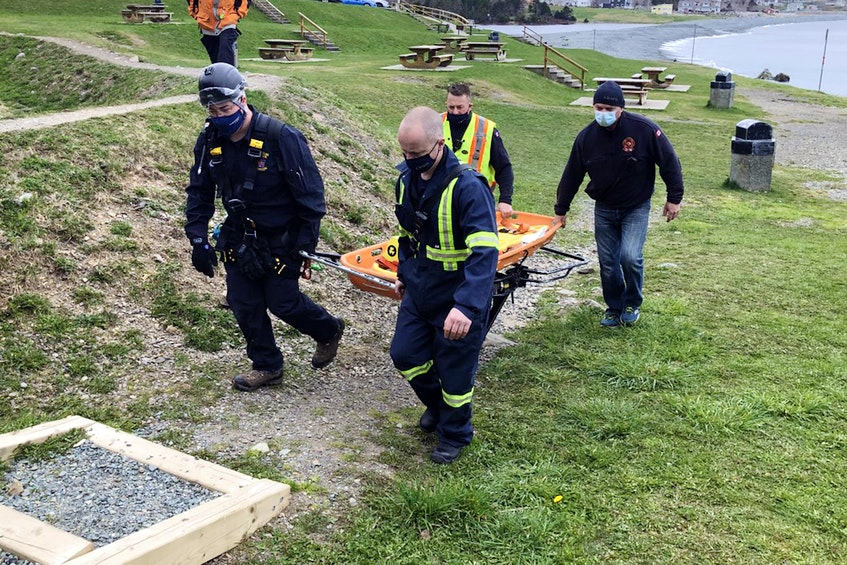 Rescuers enter the East Coast Trail at Topsail Beach to rescue an injured hiker Saturday afternoon. Joe Gibbons/The Telegram