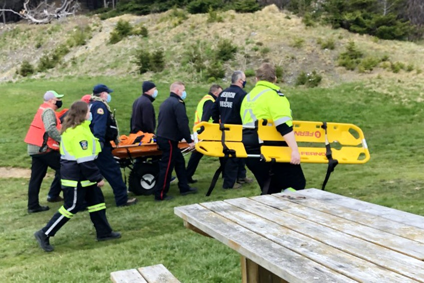Rescuers emerge from the East Coast Trail at Topsail Beach with an injured hiker Saturday afternoon. Joe Gibbons/The Telegram