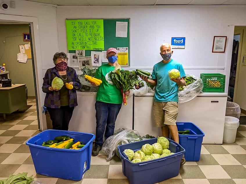 A volunteer, Glace Bay garden coordinator Kimberly McPherson and Blue Heron Farm owner Leonard Vassallo unpack donated food from Vassallo's farm. CONTRIBUTED