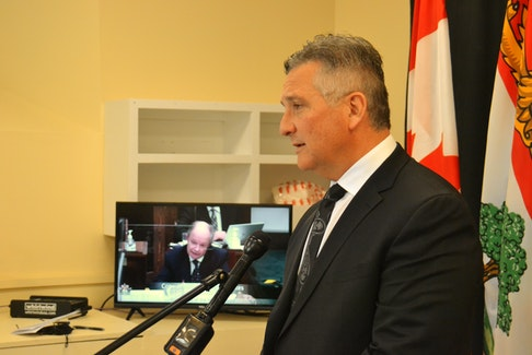 Heath MacDonald speaks to reporters, as Health Minister Ernie Hudson speaks during estimates on the legislature floor. on Friday. MacDonald surprised the minister by tabling an internal memo proving surgeries at PCH will be deferred this weekend.