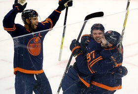 The Edmonton Oilers Connor McDavid (97) celebrates his 100th point with Leon Draisaitl (29) and Darnell Nurse (25) against the Vancouver Canucks at Rogers Place in Edmonton on Saturday, May 8, 2021.