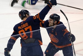 The Edmonton Oilers' Connor McDavid (97) celebrates his 100th point in 53 games with teammate Leon Draisaitl (29) against the Vancouver Canucks at Rogers Place in Edmonton on Saturday, May 8, 2021.