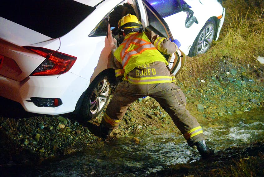 Firefighters check on a female driver following a crash at the Peacekeepers Way/Pitts Memorial cloverleaf Saturday night. Keith Gosse/The Telegram