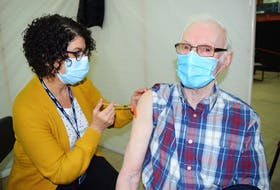 Dougie Gouthro, 84, of Gardiner Mines, happily receiving his first dose of the Pfizer-BioNtech vaccine from Claudia AuCoin, an LPN with Public Health, at the Canada Games Complex at Cape Breton University in Sydney on March 10. Vaccinations rolled out in early March for Nova Scotians ages 80 and older. Sharon Montgomery-Dupe/Cape Breton Post