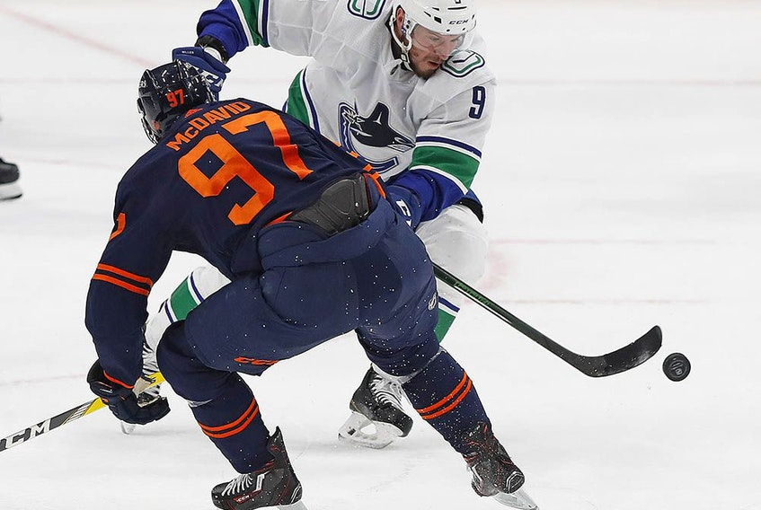 Vancouver Canucks forward J.T. Miller chips the puck past Oilers forward Connor McDavid in the second period.