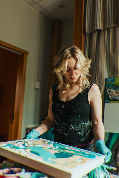 In her Tantallon studio, artist Kristen Herrington works on the latest painting in her series of #LocalPayItForward artworks, which she'll make public this week. - Erin Bulger