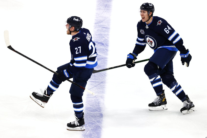 Winnipeg Jets defenceman Logan Stanley (64) celebrates the overtime goal by Winnipeg Jets left-winger Nikolaj Ehlers (27) against the Edmonton Oilers in Game 3 of the first round of the 2021 Stanley Cup Playoffs at Bell MTS Place in Winnipeg on May 23. - James Carey Lauder