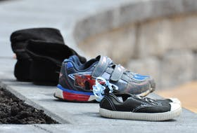 Three pairs of children's shoes sit on a wall surrounding the new Missing and Murdered Indigenous Women and Girls commemorative garden outside the Qalipu office in Corner Brook on Tuesday. The little black pair with the blood ribbon on them has the number 215 written on the toe to signify the 215 Indigenous children whose bodies were recently found buried on the site of a former residential school in Kamloops, B.C. Diane Crocker • SaltWire Network