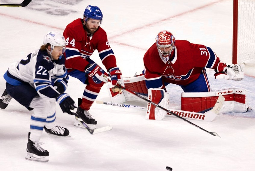 Montreal Canadiens defenceman Joel Edmundson battles Winnipeg Jets centre Mason Appleton as Carey Price follows the play during Game 3 in Montreal on June 6, 2021.