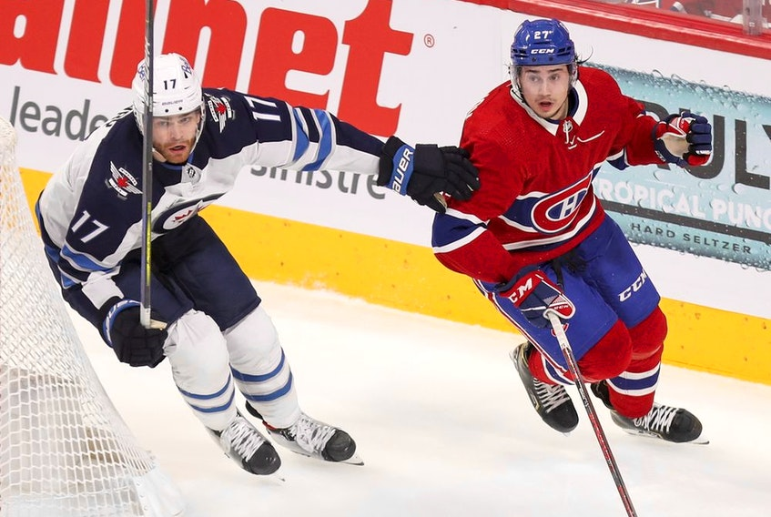 Canadiens' Alexander Romanov and Jets' Adam Lowry skate behind the Montreal net during Game 4 Monday night at the Bell Centre.