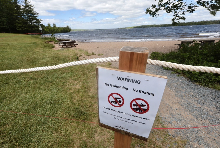 A warning sign and a red fire tape is all that's left after Halifax Fire and Emergency comb the waterfront along Grand Lake to take test samples of the water. Since officials aren't sure what the source of the water issues are, no access for the media is possible.