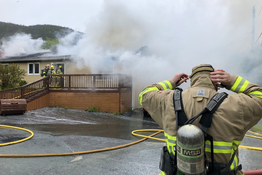 A member of the Portugal Cove St. Philip's Volunteer Fire Department checks his gear as more firefighters move into a house fire on Harding's Hill in Portugal Cove-St. Philip's on June 10.