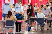 People eligible for a second COVID-19 vaccination shot wait in line at the Palais des congrès vaccination site in Montreal on June 6, 2021.