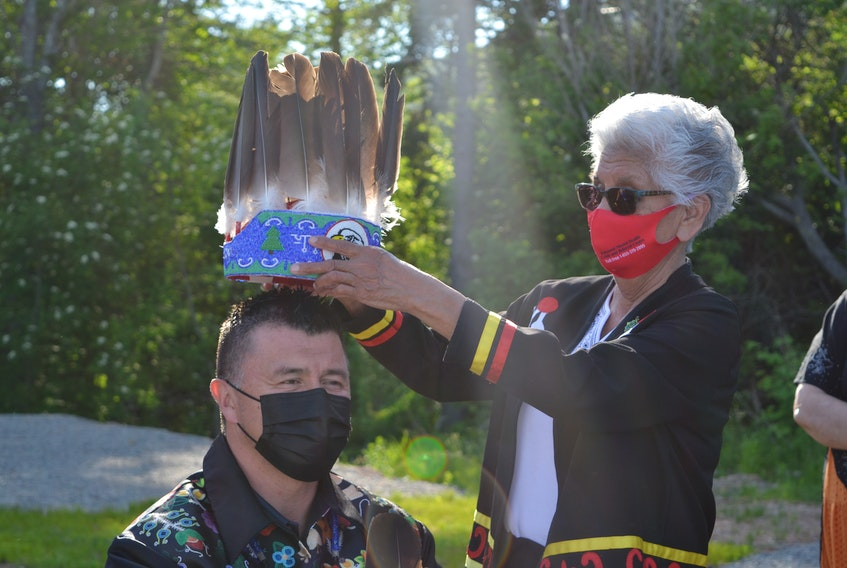 Eskasoni Chief Leroy Denny receives the traditional chief's headdress for his fifth term by community elder and residential school survivor Georgina Doucette during the inauguration ceremony on Wednesday evening. ARDELLE REYNOLDS • CAPE BRETON POST
