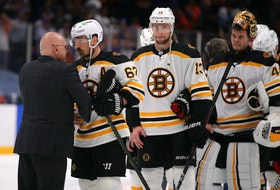 New York Islanders head coach Barry Trotz talks to Boston Bruins centre Brad Marchand (63) after the Islanders defeated the Bruins in Game 6 of the second round of the 2021 Stanley Cup Playoffs at Nassau Veterans Memorial Coliseum.