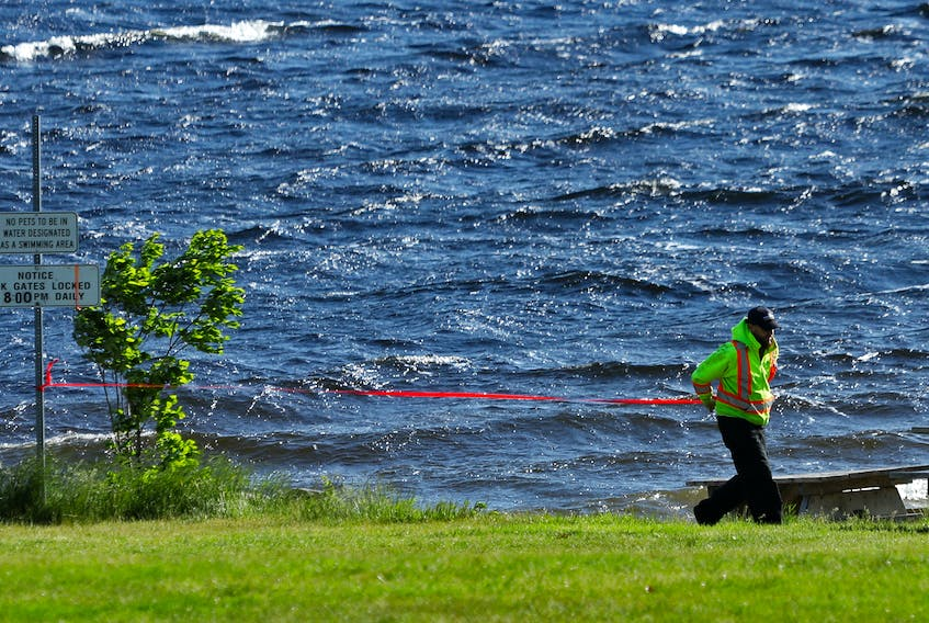 FOR NEWS STORY: A parks employee puts up caution tape across the beach at Oakfield Park in Grand Lake....the lake is now closed to all boating, fishing, swimming etc....for CAMPBELL STORY.