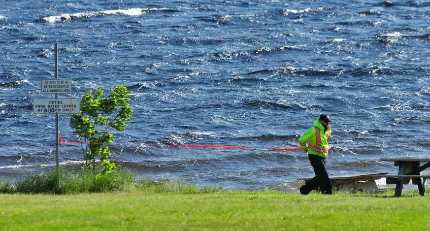 A park employee puts up caution tape across the beach at Oakfield provincial park in Grand Lake on Thursday, June 10, 2021. - Tim Krochak