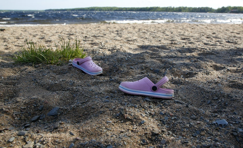 A child's pair of sandals is seen on the beach at Oakfield provincial park in Grand Lake on Thursday, June 10, 2021. The lake is now closed to all boating, fishing, swimming, etc. - Tim Krochak