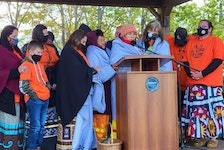 Residential school survivors and loved ones stand on stage at Confederation Landing for a closing prayer at Thursday's ceremony in honour of residential school victims and survivors.