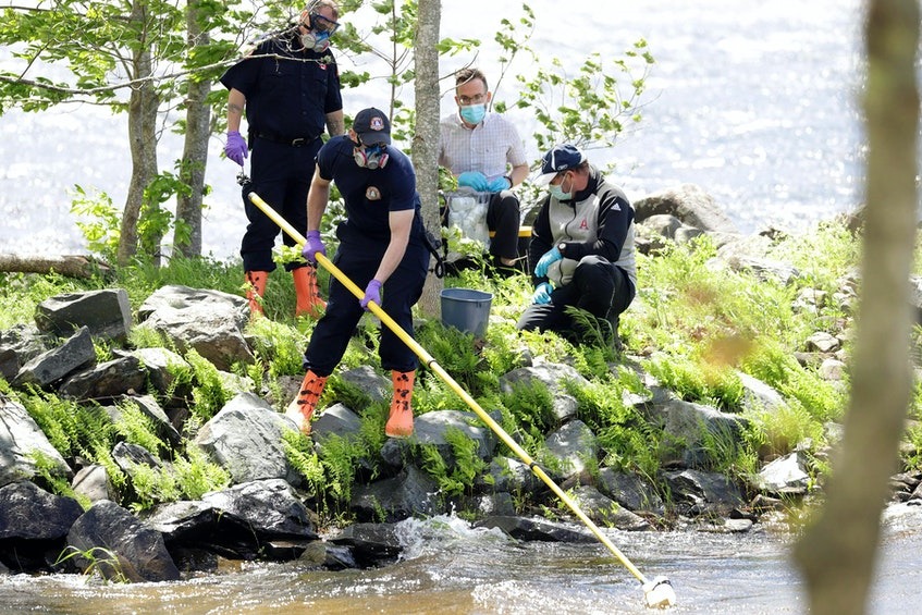 Staff from the provincial Environment Department, assisted by members of Halifax Regional Fire & Emergency, Grand Lake Station, take water samples from Grand Lake Thursday to test for toxins. - Communications Nova Scotia