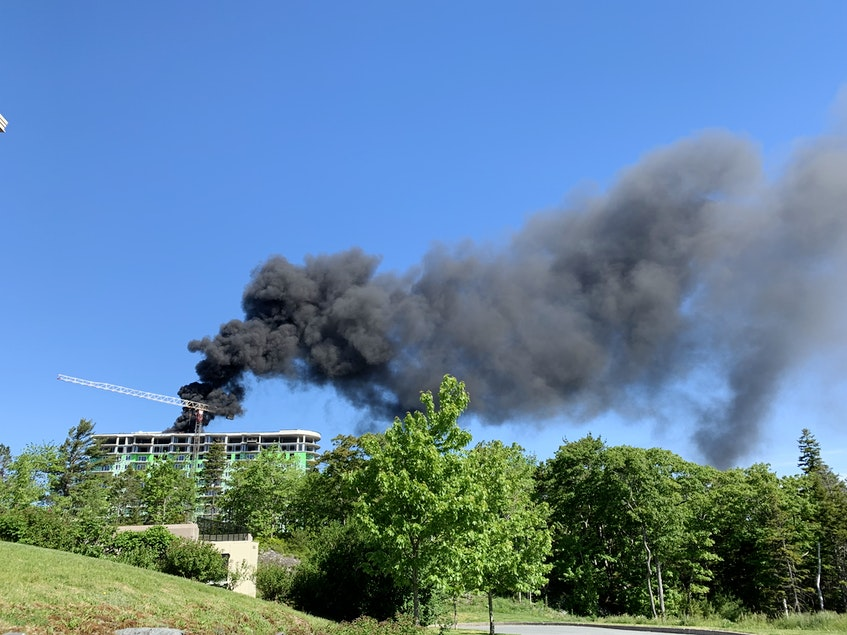 Black smoke floods out from a fire on the roof of a building under construction in the 300 block of Larry Uteck Boulevard in Halifax, N.S., on Friday, June 11, 2021. - Nicole Munro