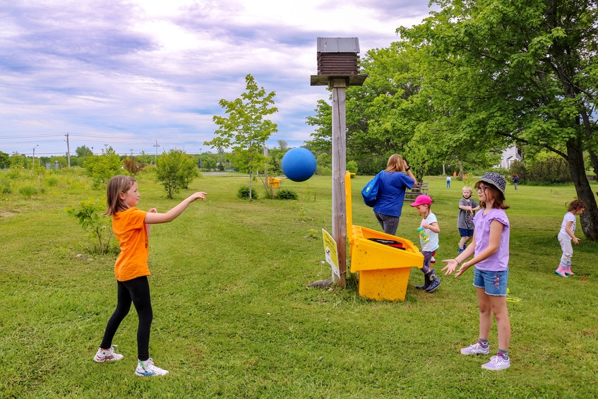 Nia Neville, left, and Stella Burns, right, play with a ball from the Busy Bees Playbox, at Southend Public Gardens in Sydney. JESSICA SMITH/CAPE BRETON POST - Jessica Smith