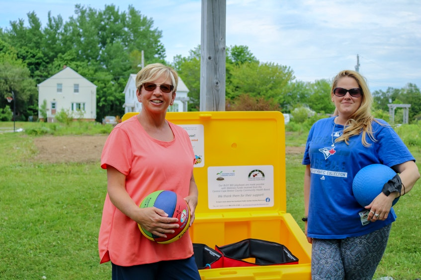 YMCA after-school program workers Karen Harriet, left, and April Madden, right, at one of the Busy Bees Playboxes, bins that are filled with toys for public use, in the Southend Public Gardens in Sydney. JESSICA SMITH/CAPE BRETON POST - Jessica Smith