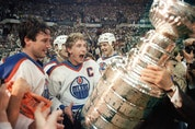 Oilers captain Wayne Gretzky and Paul Coffey get ready to hoist the Stanley Cup during the presentation in Edmonton on May 31, 1985.